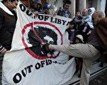 图为一名男子一脚踢破了卡扎菲的画像。(Stringer: CARL COURT / 2011 AFP)