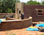 2011年11月2日,尼日利亚北部卡杜纳(Kaduna)附近的宝特瓶屋原型正兴建造中。(图片来源:AMINU ABUBAKAR/AFP)