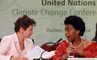 """经过长达30个小时会议后,联合国气候会议于11日在南非城市德班闭幕,与会各方达成了一份被称作""""德班平台""""的协议文件,决定建立德班增强行动平台特设工作组、实施《京都协议书》第二承诺期并启动绿色气候基金。(STR: RAJESH JANTILAL / AFP ImageForum)"""
