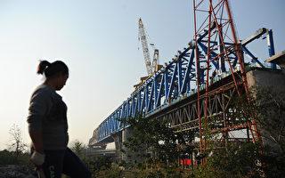 """长期以来,大陆""""豆腐渣""""工程层出不穷,高铁、地铁、高速公路等工程造价虚高。近日,中国大陆最高检察院曝出中国工程建设的秘密,高达三分之一工程款被用于行贿。图为安徽省合肥市,一位工人在高铁施工现场。(STR/AFP/Getty Images)"""