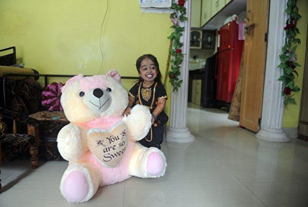 印度女孩艾姆格(Jyoti Amge)出生时仅3磅,不到一般婴儿的一半,她罹患名为软骨发育不全的侏儒症,但她笑口常开,一点也不为此自卑或丧志,她的生命宛如一个奇迹。(STR: PUNIT PARANJPE / AFP ImageForum)