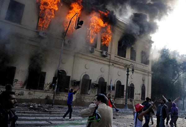 埃及军队在群众反军政府示威的第二天(17日),抗议群众与军警冲突升级,示威者投掷石块,摧毁物品。(STR: MOHAMMED HOSSAM / AFP ImageForum)