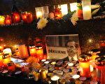 捷克首都布拉格数千民众冒着落雪和严寒,手持蜡烛来到巿中心广场集会,一起唱国歌哀悼这位捷克的伟人。(STR: MICHAL CIZEK / AFP ImageForum)