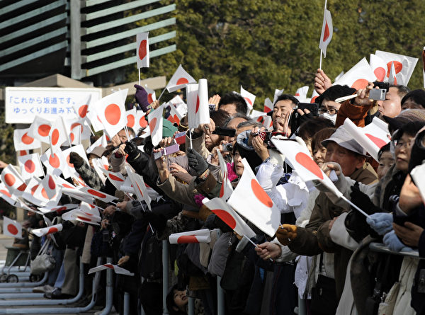 2012年1月2日,參加民眾揮舞日本國旗。(AFP PHOTO / TOSHIFUMI KITAMURA)