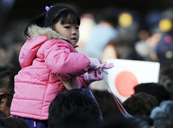 2012年1月2日,一位日本小女孩隨大人參加活動。(AFP PHOTO / TOSHIFUMI KITAMURA)