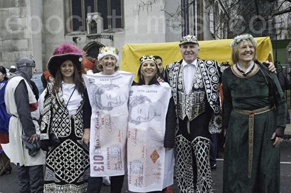 穿著印有女王頭像英鎊圖案的服裝參加遊行的人們,表示對今年英女王登基60週年慶典的祝賀。(攝影:梁思成/大紀元)