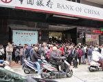 高士德红街市中国银行分行门前,聚集了大批等候换龙年新钞的民众,在得知没有龙钞换后,仍然不愿离去。(摄影:许侠/大纪元)