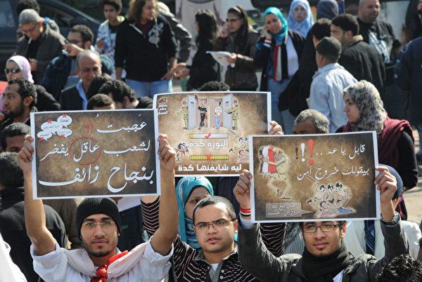 2012年1月25日,埃及首都开罗:埃及示威者聚集在塔里尔广场上集会纪念起义推翻穆巴拉克独裁政权一周年的日子,图为示威者展示其标语。(AMRO MARAGHI /AFP)