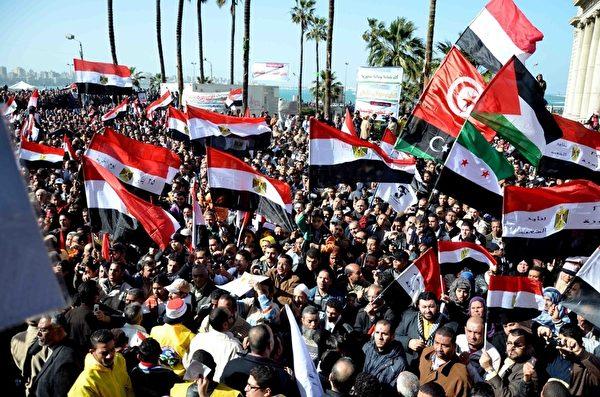 2012年1月25日,埃及首都开罗:上万的埃及示威者聚集在塔里尔广场上集会纪念起义推翻穆巴拉克独裁政权一周年的日子,图为示威者挥舞埃及以及利比亚,突尼斯,叙利亚和巴勒斯坦的国旗。(KHALED DESOUKI/AFP)