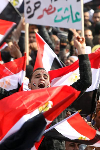 2012年1月25日,埃及首都开罗:上万的埃及示威者聚集在塔里尔广场上集会纪念起义推翻穆巴拉克独裁政权一周年的日子,图为示威者挥舞国旗。(KHALED DESOUKI/AFP)