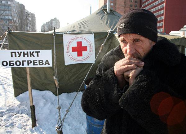 """欧洲今年冬季特别严寒,最低温度已降至摄氏零下33度左右,因天寒地冻不幸丧生的人数上升到160人,""""世界气象组织""""已对东欧多国发布红色警戒。图为乌克兰一名无家可归的人在收容所门口。(Alexander KHUDOTEPLY / AFP)"""