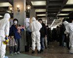 圖為福島電廠反應爐在2011年3月發生爆炸造成輻射外洩後,穿上防輻衣的人員正為撤離災區的民眾進行輻射汙染檢測。(攝影:KEN SHIMIZU/AFP/Getty Images)