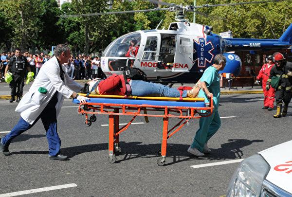 2月22日,阿根廷首都布宜諾斯艾利斯發生一起嚴重火車事故,已經有49人死亡,圖為救援人員運送傷患。(HUGO VILLALOBOS / AFP)