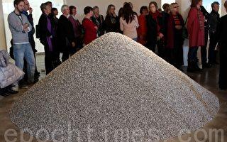 瑞典游客正在听导游讲解艾未未的《葵花籽》(摄影:李志河/大纪元)
