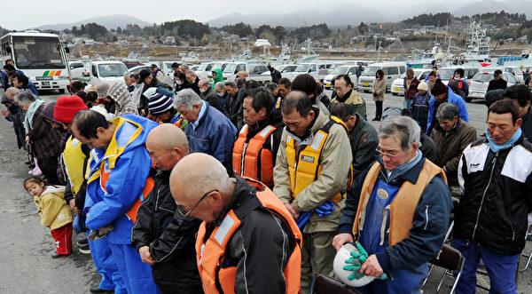 2012年3月10日,宮城縣氣仙沼市,民眾為罹難者默哀。(KAZUHIRO NOGI/AFP)