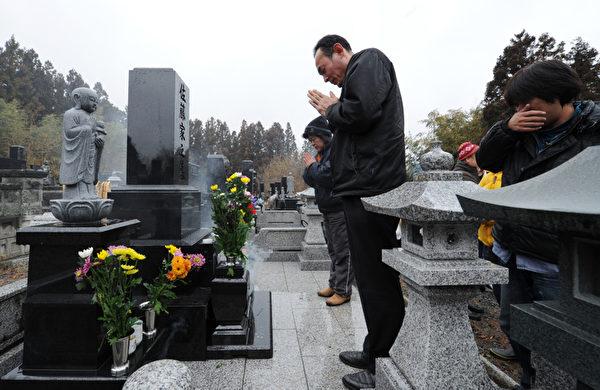 2012年3月10日, Minamisanriku, Miyagi,罹難者親屬在墳前祭拜。( KAZUHIRO NOGI / 2012 AFP)