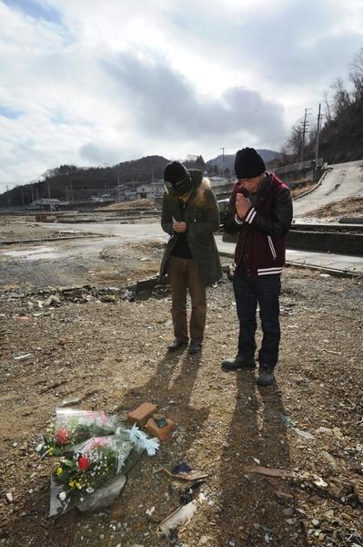 2012年3月11日,宮城縣女川町,民眾以鮮花悼念在地震海嘯中罹難的親屬。(KAZUHIRO NOGI/AFP)