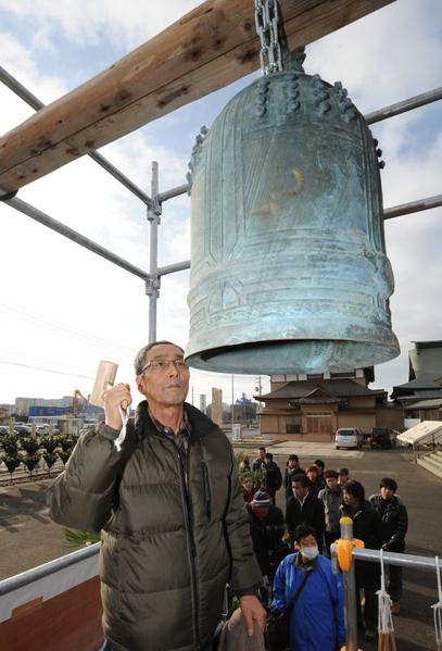2012年3月11日,宮城縣石卷市,民眾擊鐘為死難者祝禱。(KAZUHIRO NOGI/AFP/Getty Images)