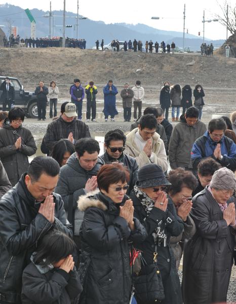 2012年3月11日,宮城縣石卷市,民眾為罹難者默哀。(KAZUHIRO NOGI/AFP)