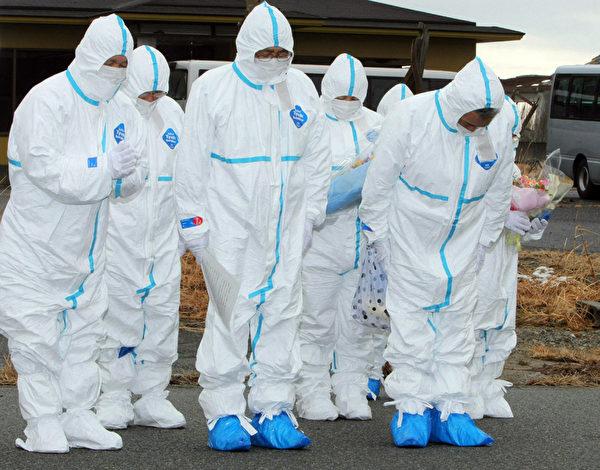 2012年3月11日,福島縣 Okuma,當地居民穿著防護衣,為罹難者默哀。(STR/AFP/Getty Images)