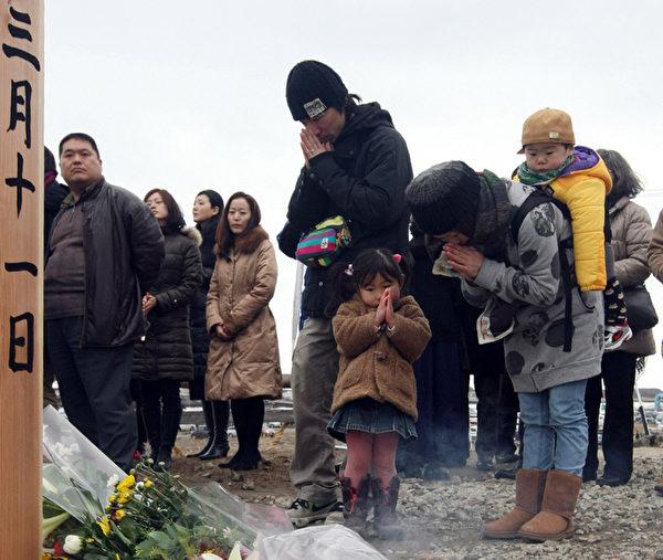 2012年3月11日,宮城縣名取市,民眾為罹難者默哀。( AFP)