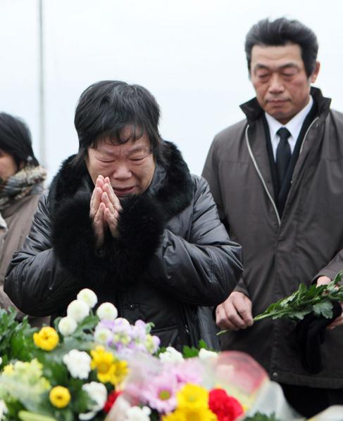 2012年3月11日,宮城縣氣仙沼市,民眾以鮮花悼念罹難親屬 。(AFP)