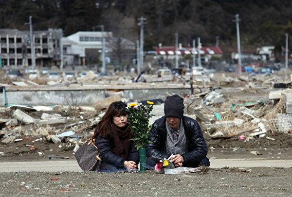 2012年3月11日,宮城縣氣仙沼市, 民眾以鮮花悼念罹難親屬。(STR/AFP/Getty Images)