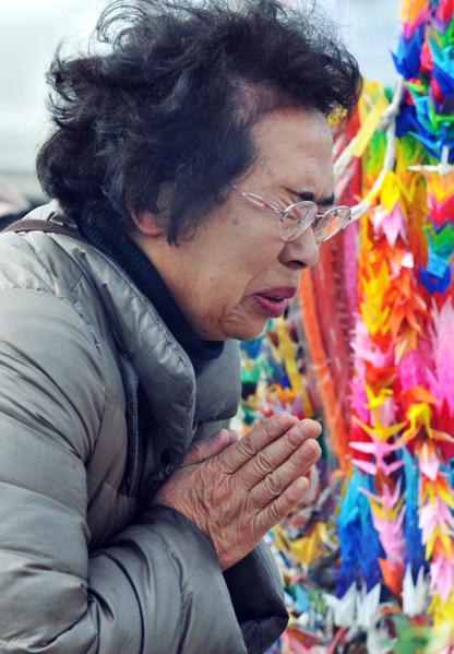 2012年3月11日,宮城縣石卷市,一位年長婦女悼念罹難的親屬,神情哀傷。  (KAZUHIRO NOGI / 2012 AFP)