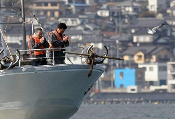 2012年3月11日,岩手縣大船渡市,漁民在船上為罹難者默哀。 (STR/AFP/Getty Images)