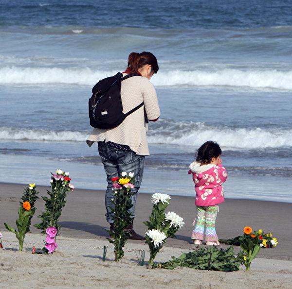 2012年3月11日,宮城縣仙台,一位母親帶著女兒在海邊悼念罹難者。(AFP)