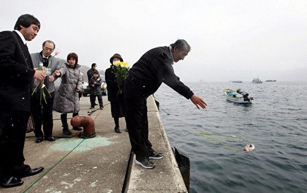 2012年3月11日,岩手縣大槌町,一位名叫Teruo Shirogane的先生,投擲鮮花悼念其罹難的妻女。(AFP)