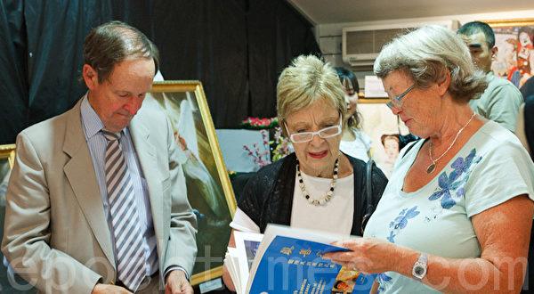 南澳省Holdfast Bay市长罗兰(左一)夫妇与参观者一同观看美展画册。(摄影:戴宁 / 大纪元)