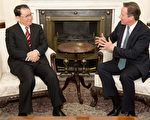 """英国首相卡梅伦(右)17日在唐宁街首相府会见到访的中共政治局常委李长春(左)。卡梅伦敦促中方,""""全面而恰当""""调查英国商人海伍德在重庆的死亡案件。(LEON NEAL/AFP)"""
