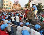 尼泊尔加德满都庆祝战车节,民众4月25日拖拉着巨型战车上街游行,祈求风调雨顺、谷物丰收及繁荣好运。(Prakash MATHEMA/AFP)
