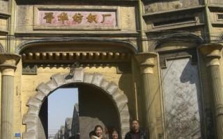 老晋华纺织厂的大门,门后可见上世纪二十年代的厂房和库房。前面老人是作者的妹妹 张文采,她左右各一人,是她的孩子及孙子。(作者提供之近日相片)