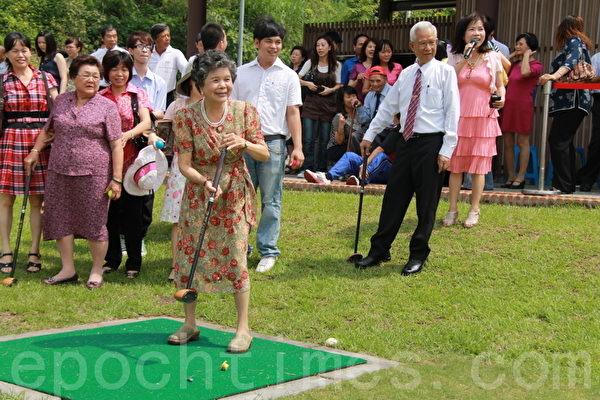 模範母親大忠村魏秀女士接受五星級表揚,以及初體驗高爾夫球揮桿。(攝影:郭千華/大紀元)