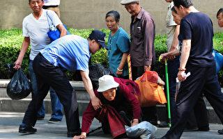 朝阳医院门外,陆续赶到了很多访民,有的声援陈光诚,有的诉说着自己陈年的冤情。不过全部遭警察驱离。摄于5月8日。(MARK RALSTON/AFP)
