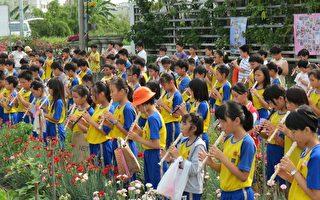 四年级花香班小朋友在花田里吹奏庆收割。(摄影:李撷璎/大纪元)