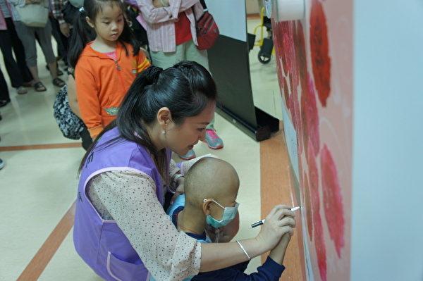 藝人張鳳書9日協助年紀僅4歲的癌童簽名,看著自己在畫作上的名字,癌童笑得很開心。(癌症希望基金會提供)