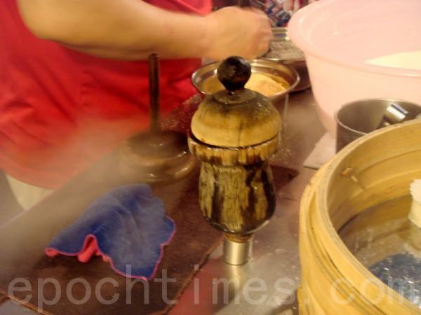 容器插入蒸氣座,蓋上小蓋子,用熱騰騰的蒸氣,約15秒可蒸熟蓬萊米粉。(攝影: 彩霞/大紀元)