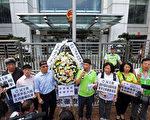 香港民主党约十名成员星期五在中联办门外摆放花牌及默哀,撒酒祭奠李旺阳。(摄影:潘在殊/大纪元)