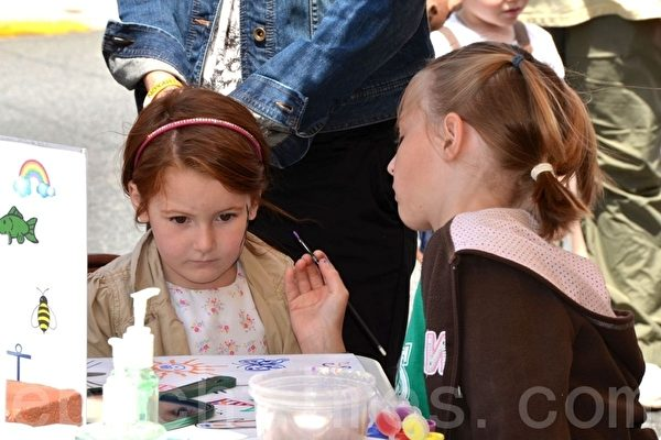 小朋友在專心地給小朋友畫臉。(攝影:良克霖/大紀元)