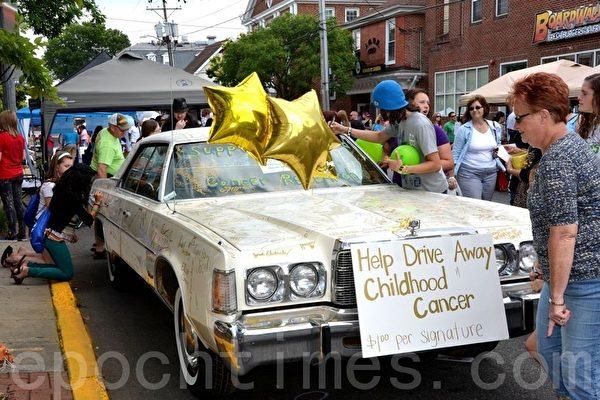 民眾在車體上簽名以幫助患癌兒童。(攝影:良克霖/大紀元)