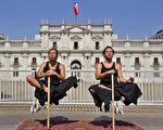 """2008年4月3日,在智利首都圣地亚哥,魔幻艺术家尼古拉斯.路易赛提(左)与约翰.保罗.奥拉韦里在莫内达宫前表演""""悬空术""""。(AFP)"""