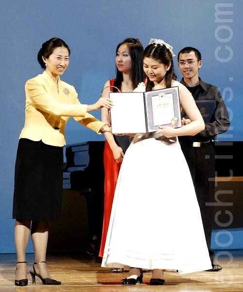 2008年新唐人全球系列大賽組委會主席馬麗娟為全世界華人鋼琴大賽銀獎得主蓮娜頒發獎金和獎狀。(攝影:戴兵/ 大紀元)