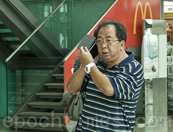 """""""香港青年关爱协会""""负责人之一在现场指挥冲击法轮功真相点,他与中国井冈山市一名特聘政协委员""""同名同姓"""",有消息称此人就是周永康阵营专程从中国派来香港负责冲击法轮功真相点的中共特工。(摄影:余钢/大纪元)"""