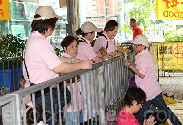 十多名身穿粉红色统一制服,上印香港青年关爱协会的帮凶,19日冲进法轮功学员真相点内,四处悬挂污蔑横幅,又大摇大摆吃东西,用尽各种方法挑衅。右二的粉红色女士,是其中一名今次冲击真相点的小头目之一。(摄影:邝天明/大纪元)
