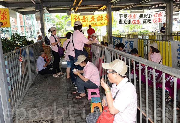 十多名身穿粉红色统一制服,上印香港青年关爱协会的帮凶,19日冲进法轮功学员真相点内,四处悬挂污蔑横幅,又大摇大摆吃东西,用尽各种方法挑衅。(摄影:邝天明/大纪元)