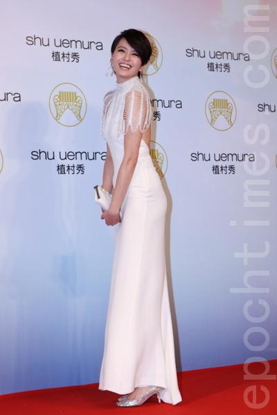 梁詠琪穿著白色高領露背禮服,串珠袖子搭配水滴耳環搖曳生姿,展現高雅的低調性感。(攝影:林伯東/大紀元)