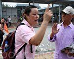 亲共团伙的一名女徒众(左)不顾法轮功学员劝善,在落马洲真相点扰攘。(摄影:潘在殊/大纪元)